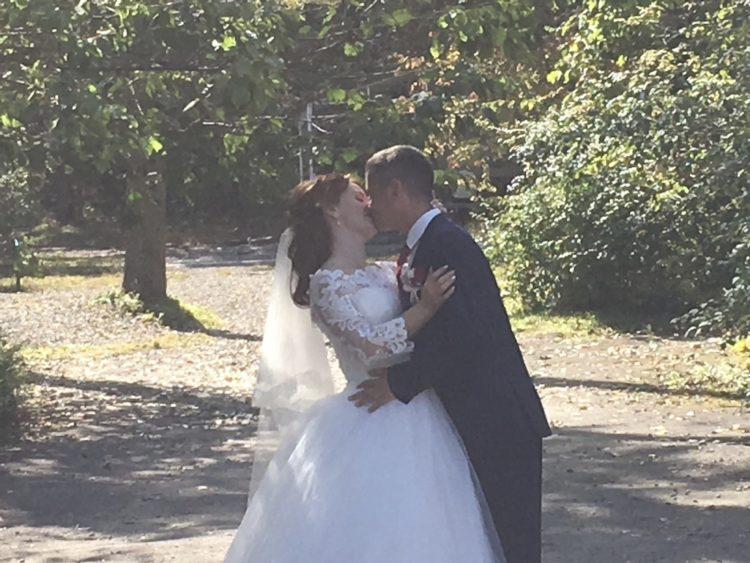 ウラジオストクのボタニカルガーデンで結婚記念撮影をするカップル