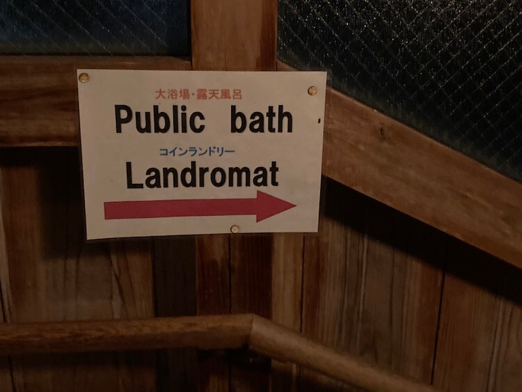 湯巡り日本一周Nバン車中泊30湯目 ホテルなはりの日帰り温泉、浴室へ続く渡り廊下にはコインランドリーの張り紙が
